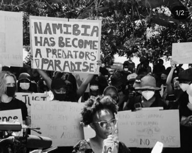 "Black and white photo at a protest in Nambia. A placard reads ""Nambia has become a predators paradise"""