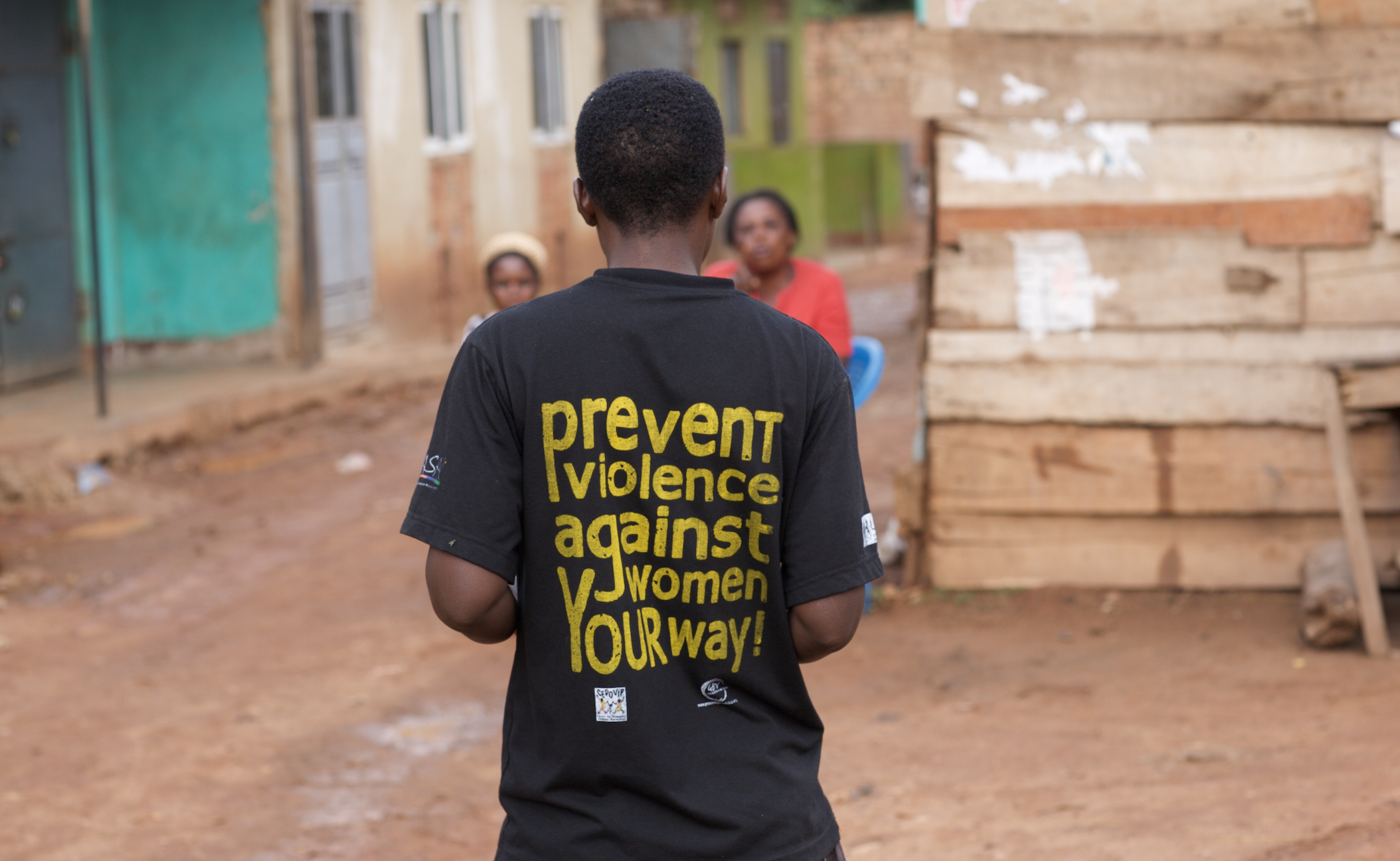 "Picture of a man standing backing the camera and wearing a black shirt that reads ""prevent violence against women your way"""