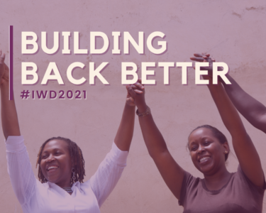 "Image of women holding hands above their hands with text ""Building Back Better, and #IWD2021"" written in white and purple"